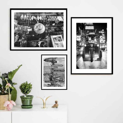 A wall gallery of 3 black and white Asia themed wall art prints above a console table.