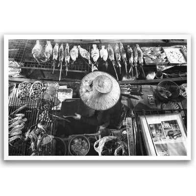 Black and White wall art print of a Bangkok Floating Market vendor on her boat grilling seafood.