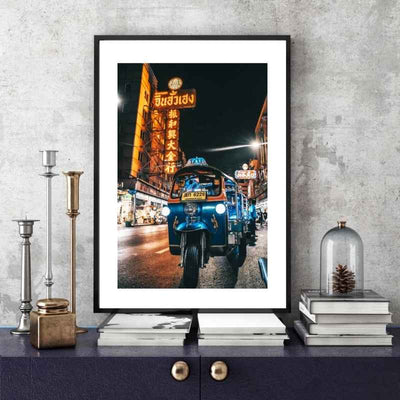 Framed wall art print of a tuk tuk parked at night on a street in Bangkok placed above a stack of books on a console table.