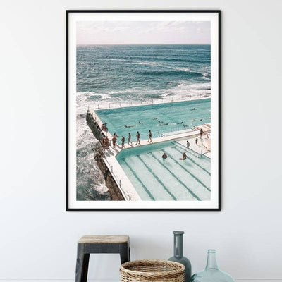 Framed wall art print of Bondi Iceberg pools with a view of the beach displayed above a stool, glass jars and a woven basket.