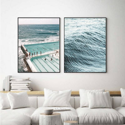 Beach themed wall art prints hanging above a white couch.