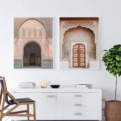 Modern white living room with 2 framed wall art print of an intricately carved and tiled Moroccan door and archway hanging above a white table .