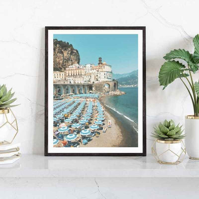 Framed wall art print of a beach in Europe with classic striped beach umbrellas and lounge chairs.