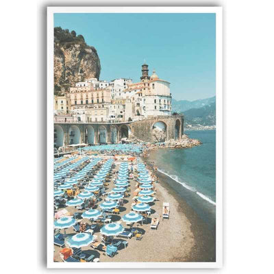 Wall art print of a beach in Europe with classic striped beach umbrellas and lounge chairs.