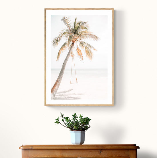 Wall art print of a swing hung on a coconut tree on the beach.
