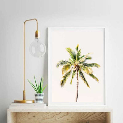 A framed wall art print of a beautiful coconut tree on top of a table with a modern lamp and a small plant.
