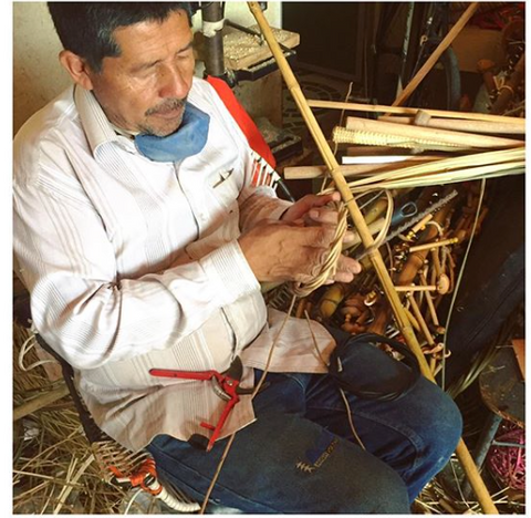 Colombian artisan working with straw for handbags