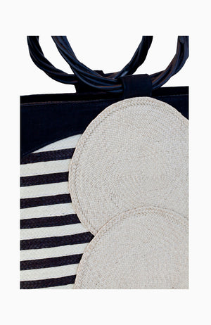 Large straw and leather tote handbag with black and white striped pattern.