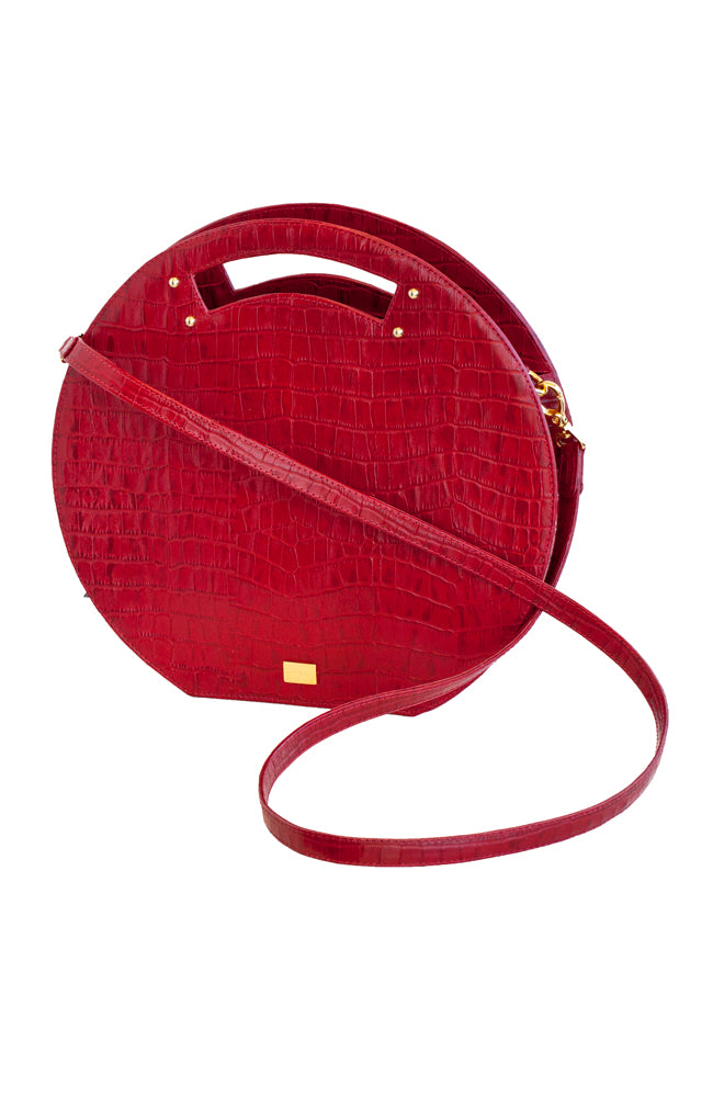 Red leather round-shaped handbag with croc design, can be worn with handle or as cross body. Handcrafted in Colombian leather with golden accents. Unique, bold, colorful and trendy, made by local artisans and designer, sustainable eco conscious fashion