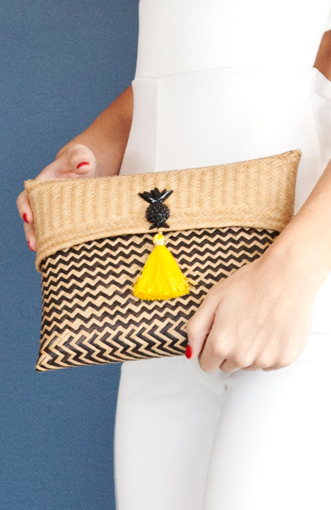 handmade straw clutch handbag dyed with natural colors black and cream with yellow tassel and pineapple ornament