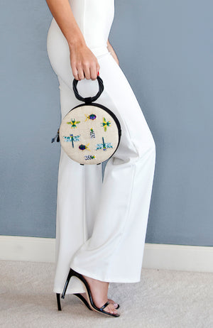 White and black round straw and leather mini handbag with colorful insect embroidery and round wood handle