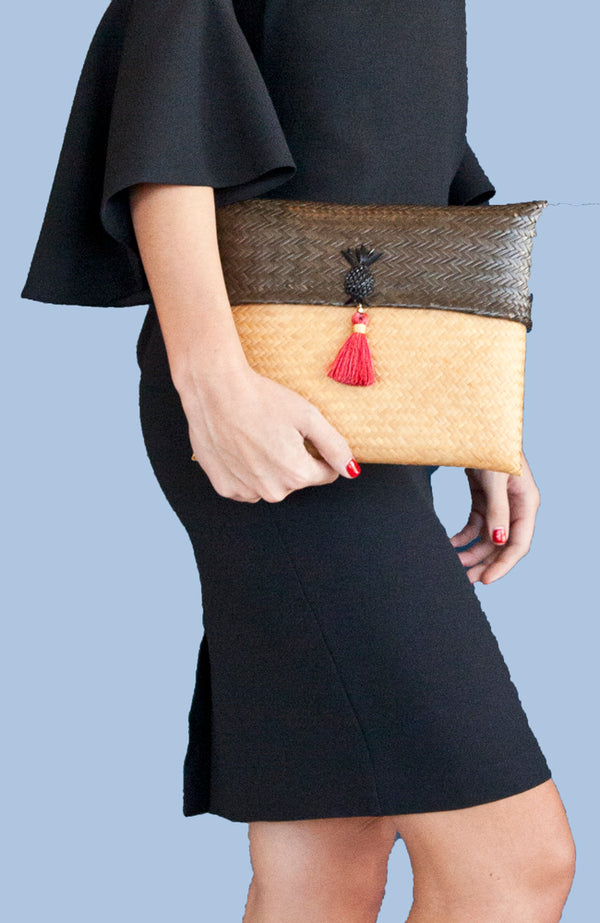 Handcrafted dark brown and cream color straw clutch handbag with pink tassel.