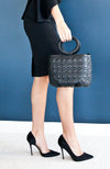 Soft leather quilted box shaped black satchel handbag with short, rounded handle.