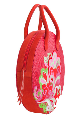 Pink straw and leather rounded zippered handbag with flower embroidery and short leather handle.