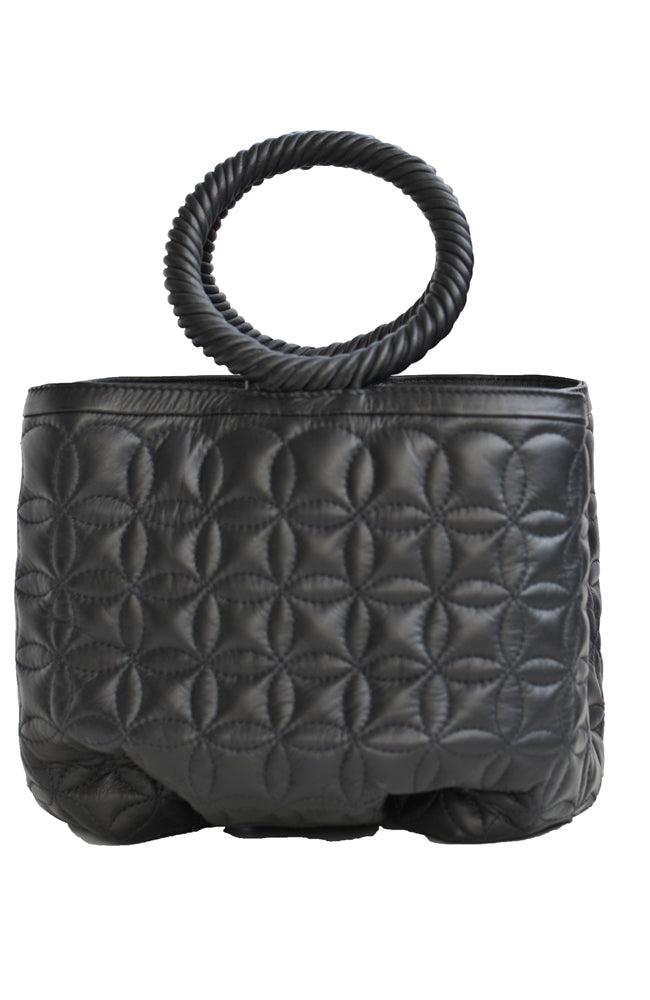 Soft leather quilted black handbag with short, round handle. Has two roomy compartments. Handmade and artisan created in Colombia by local craftsmen. Eco conscious and sustainable.  Luxurious and modern.