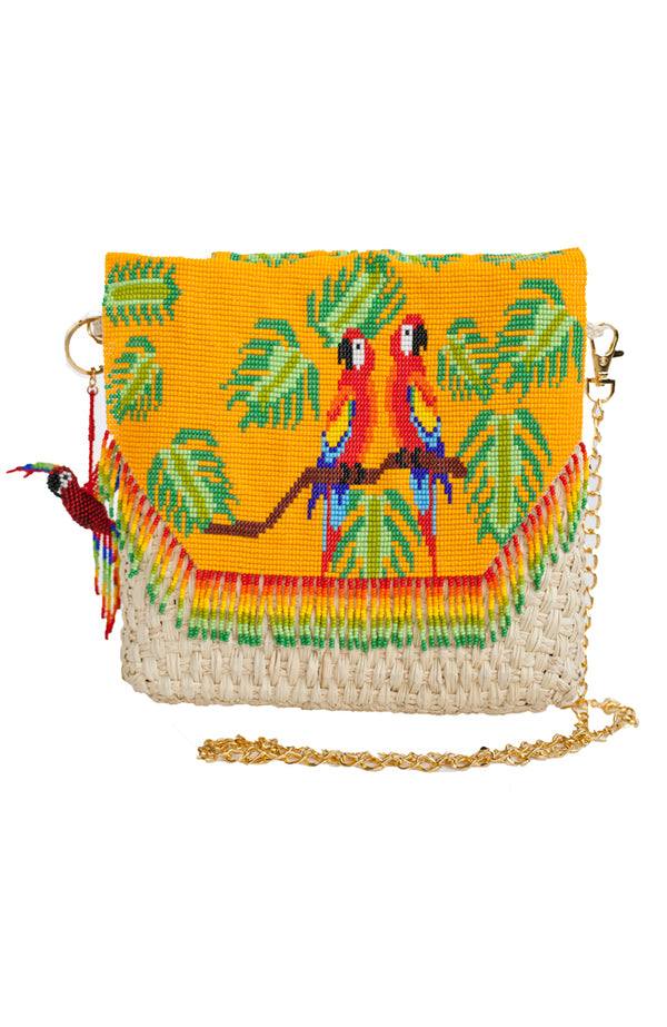 Crossbody clutch beaded straw handbag with colorful pattern of parrots and leaves.