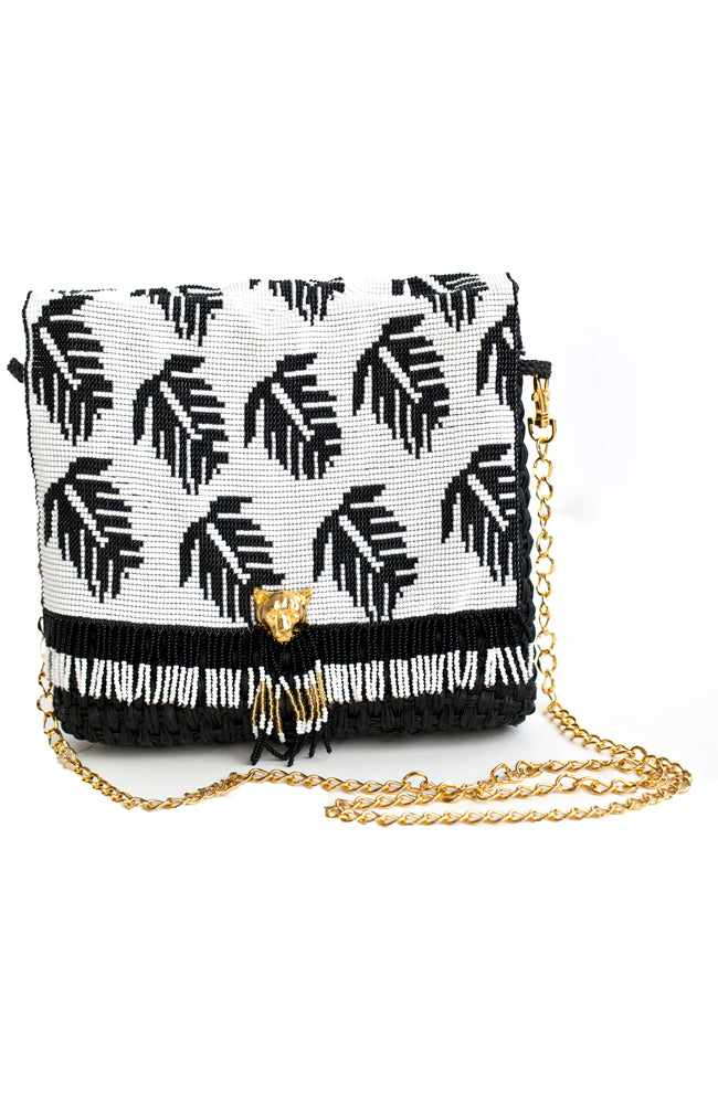 Handmade beaded straw clutch and crossbody handbag with black dyed palm fiber, 24K gold plated bronze puma face and chain, and glass beads. Patterned with black and white leaves. Sustainable and eco conscious.