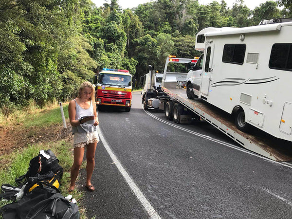 Crashed campervan being taken away while girl reads insurance documents by Fire engine
