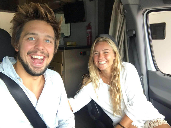 2 people sitting in the cockpit of campervan, ready to start the journey