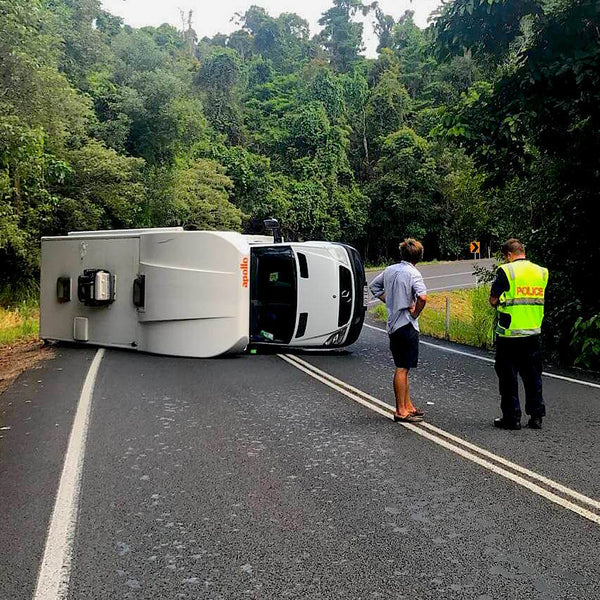 Crashed campervan on its side with police interviewing driver