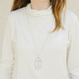 Unusual art deco inspired statement necklace worn on white top