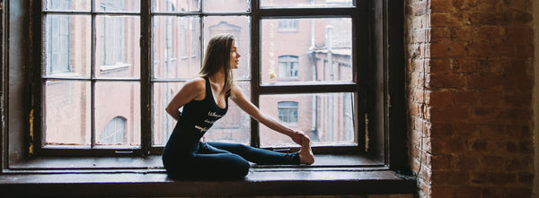 Woman in fitness wear by window by Pexels.com