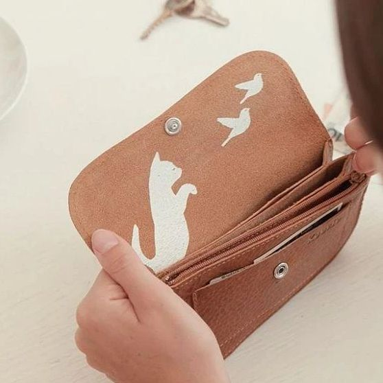 Tan leather purse with discreet cat motif under flap
