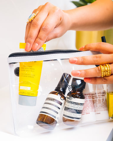 female packing toiletries and cosmetics into a clear and reusable pouch for passing through airport security