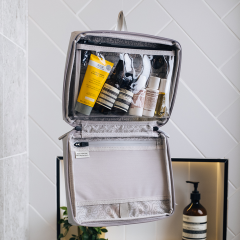 grey OneNine5 wash bag zipped open and hanging up in a bathroom. Toiletries and cosmetics are packed inside