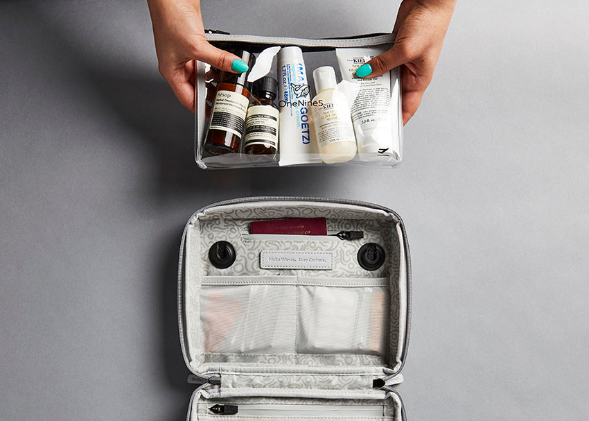 Placing clear, airport toiletry bag with, filled with cosmetics and make-up, inside Moeraki Grey travel toiletry