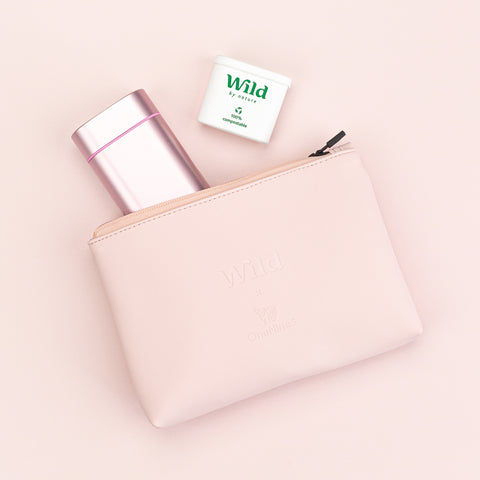 Birdseye image of the OneNine5 & Wild vegan leather, pink pouch.  zipped open with a wild deodorant & biodegradable refill poking out of the bag