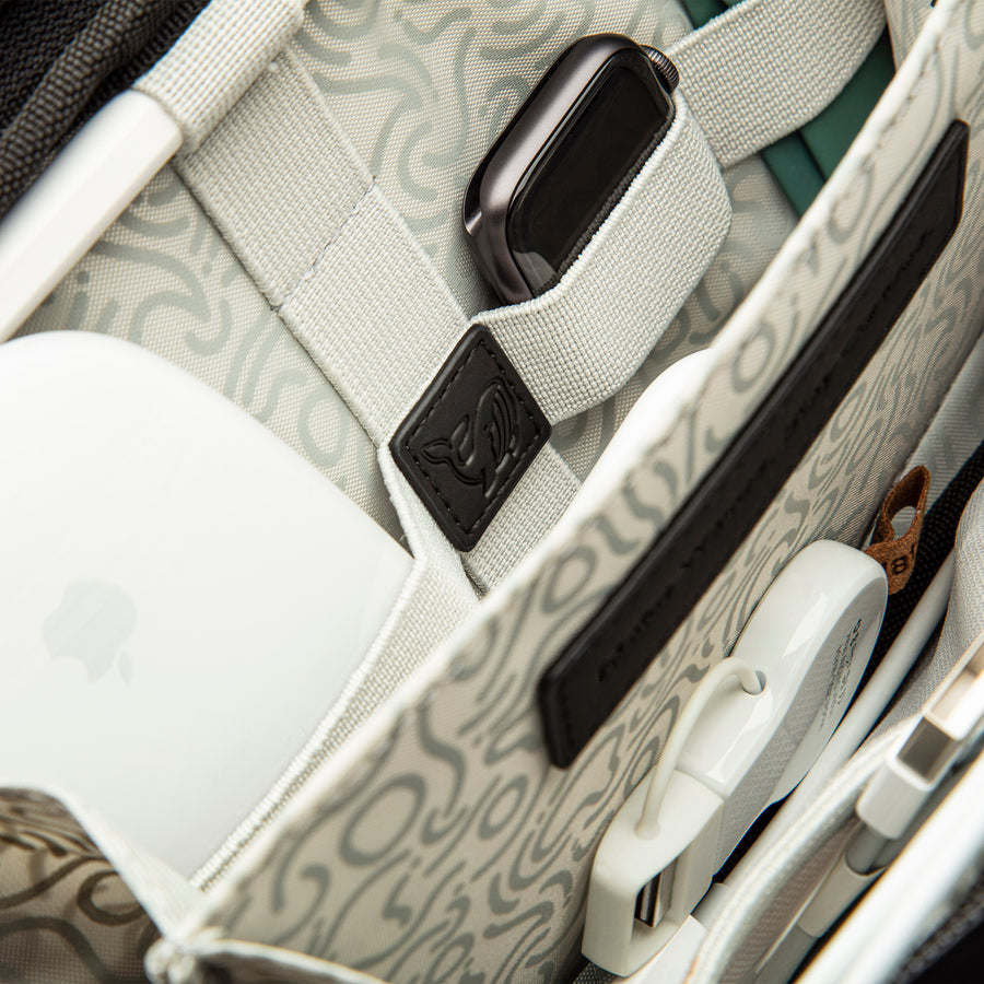 A close-up shot inside the Miho Black Tech And Wires Pouch. A black PU patch is visible which is debossed with the words 'Make Waves. Stay Curious'. Organised inside the elastic loops is a wireless Apple Mouse, an Apple Watch, Apple Watch strap. Between the dividers is an Apple Watch USB charger and other Apple cables.