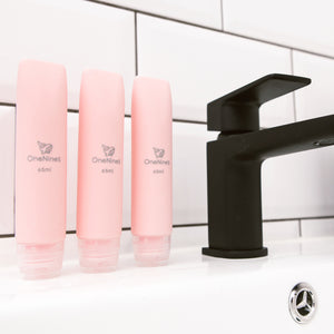 3 pack of OneNine5 pink silicone travel bottles on the bathroom sink, to the right of a black tap