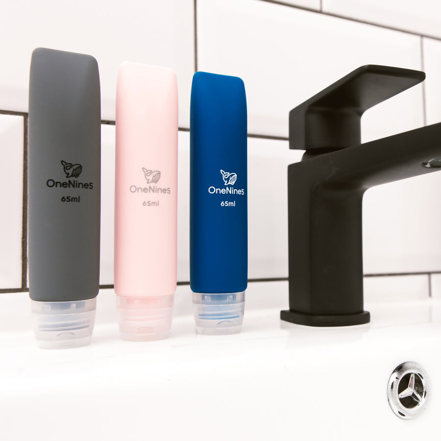 3 pack of OneNine5 mixed colour travel bottles on the bathroom sink, to the right of a black tap