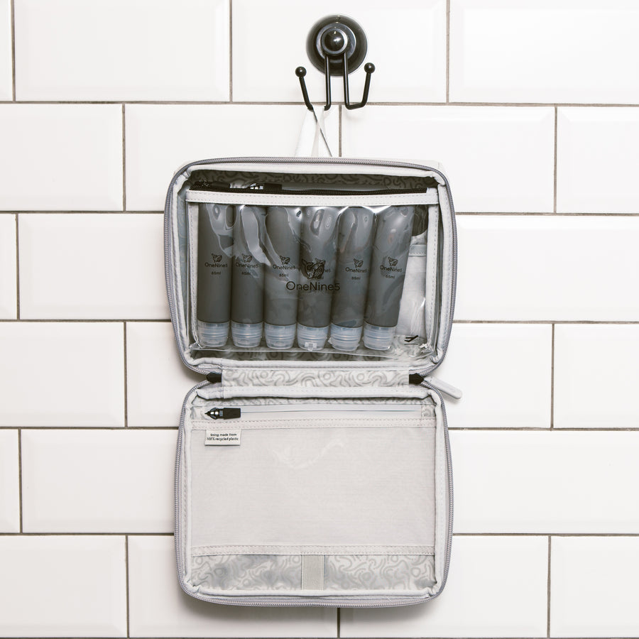 Six grey silicone travel bottles inside the clear toiletry pouch. The pouch is attached inside our OneNine5, Moeraki Grey wash bag using the hanging hook in the bathroom