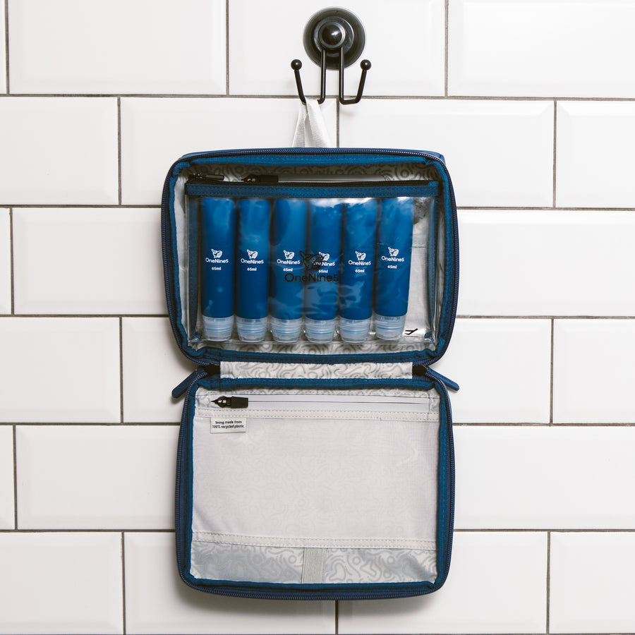 Six blue silicone travel bottles inside the clear toiletry pouch. The pouch is attached inside our OneNine5, Havelock Blue wash bag using the hanging hook in the bathroom