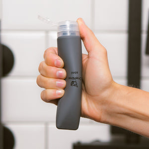Women's hand squeezing the soft silicone OneNine5 grey travel bottle, with the leakproof cap (lid) flipped open