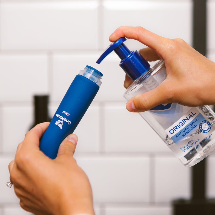 Female hands filling the wide neck of a blue OneNine5 silicone bottle with anti-bacterial hand sanitiser (gel)