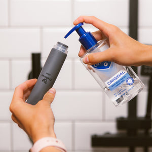 Women's hands filling the wide neck of a grey OneNine5 silicone bottle with anti-bacterial hand sanitiser (gel)