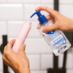 Female hands filling the wide neck of a pink OneNine5 silicone bottle with anti-bacterial hand sanitiser (gel)