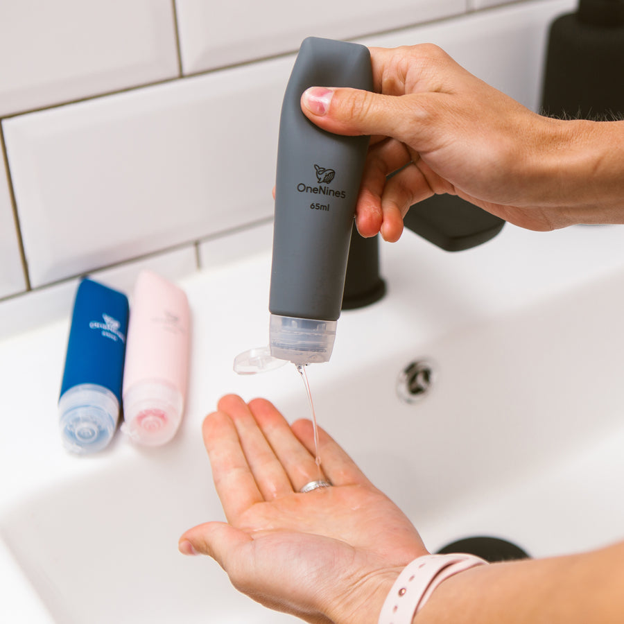 Female squeezing soap from the soft silicone OneNine5 grey travel bottle. Pink and blue reusable OneNine5 bottles are in the background resting on the bathroom sink