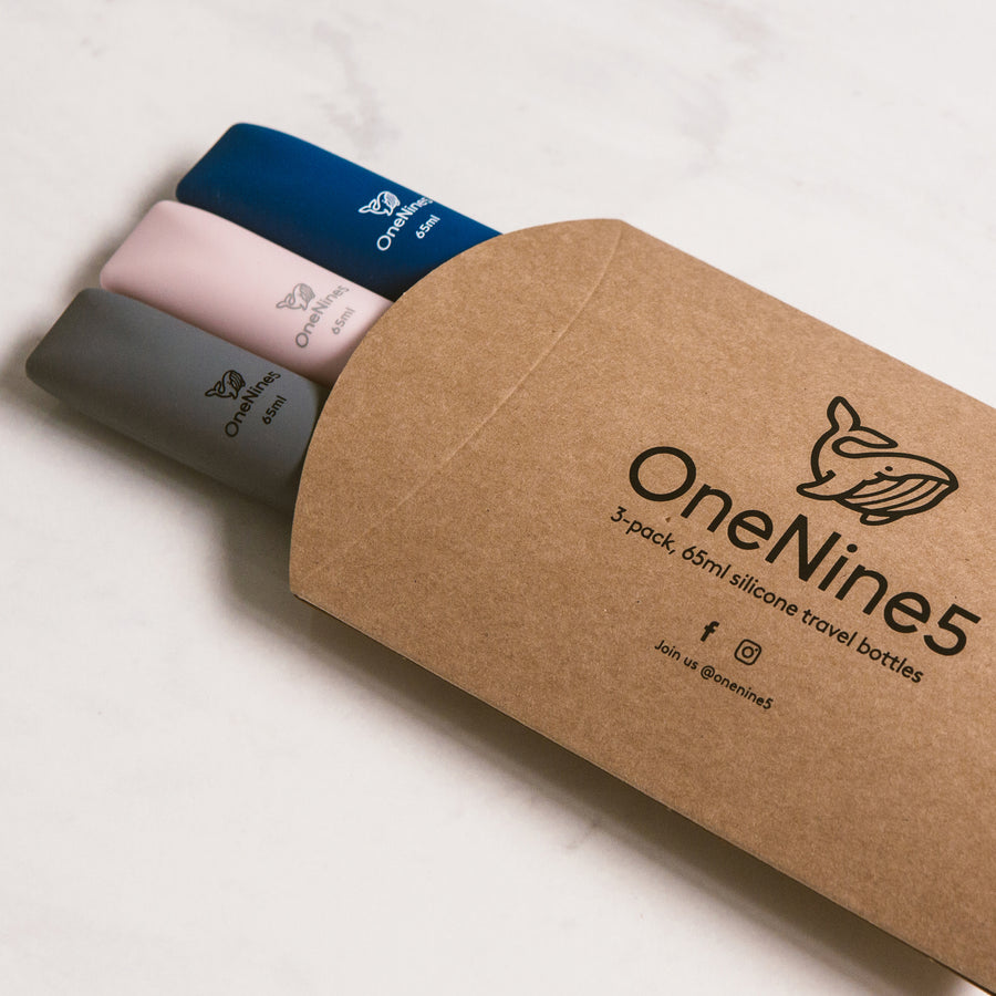 3 pack of mixed colour silicone travel bottles are packed inside brown, recyclable kraft paper. The packaging is branded with a black OneNine5 logo