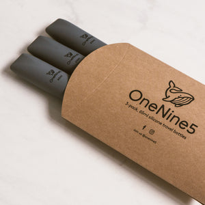 3 pack of grey silicone travel bottles are packed inside brown, recyclable kraft paper. The packaging is branded with a black OneNine5 logo