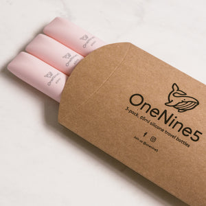 3 pack of pink silicone travel bottles are packed inside brown, recyclable kraft paper. The packaging is branded with a black OneNine5 logo