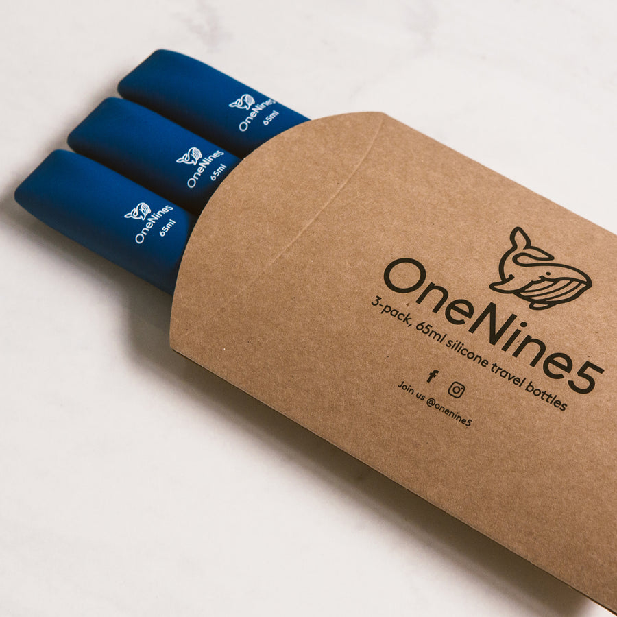 3 pack of blue silicone travel bottles are packed inside brown, recyclable kraft paper. The packaging is branded with a black OneNine5 logo