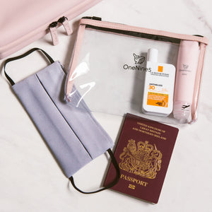 OneNine5 travel flat lay including our Komodo Pink, Eco-Conscious wash bag, clear and reusable bag to carry cosmetics and toiletries, a pink silicone travel bottle, light grey face covering, SPF and UK passport