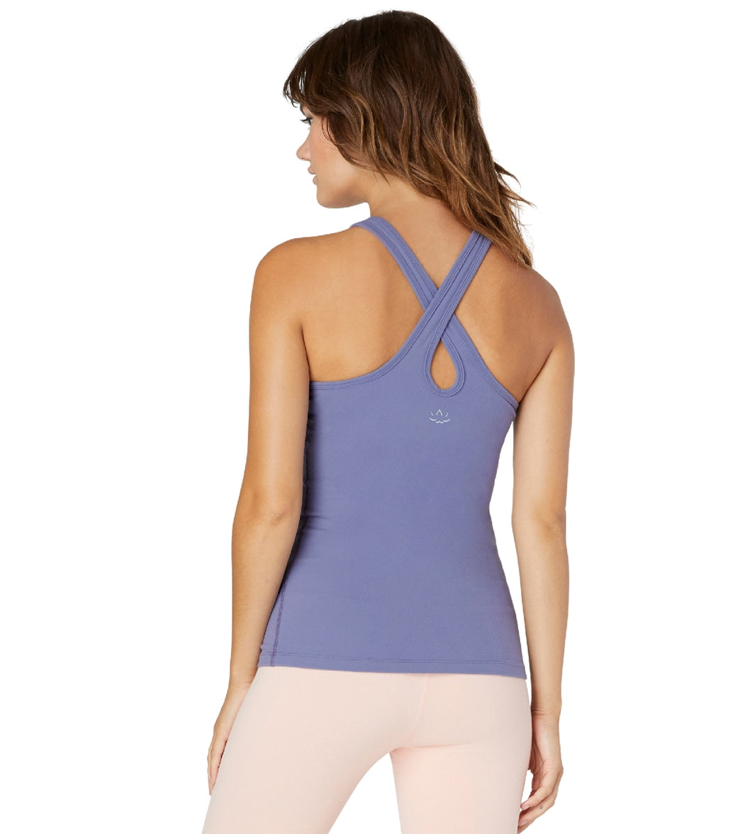 Pull-on comfortable support with this Under Lock and Keyhole Yoga Tank Top. A crisscross and keyhole back gives this second-skin tank top a stylish update. Features High-neck tank stop. High round neckline. Crisscross back with keyhole cutout. Self-lined shelf bra. Reflective Beyond Yoga logo at back center. Super soft, moisture-wicking material. Color and shape retaining. 4-way stretch material. Details Fabrics: 90% Supplex, 10% Lycra Colors: Black, Blue Style Features: High Neck, Crisscross, K