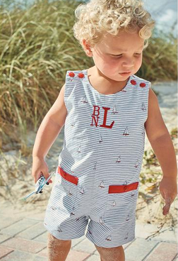 Boy wearing a navy and white striped romper with red buttons and trim