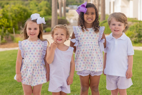 Group of children wearing James Lottie shorts, shirts, and rompers