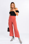 black off the shoulder button front crop top, off the shoulder top, coral high waisted trousers, snakeskin booties, pointed toe booties